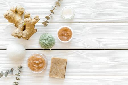 Scrubs and creams for homemade spa. Organic cosmetics with herbs, ginger on white wooden background top view mockup