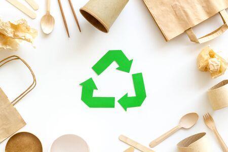 Simbolo di riciclaggio e immondizia di carta su sfondo bianco vista dall'alto Archivio Fotografico