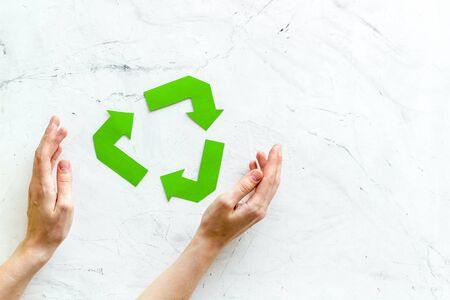Recycling symbol in hands on white marble background top view 版權商用圖片