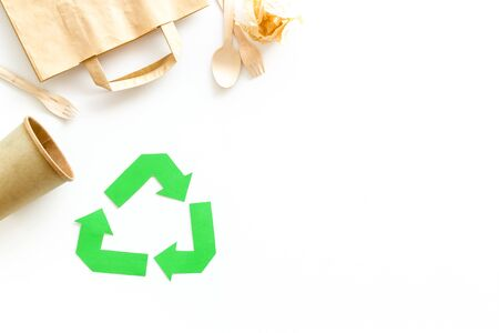Recycling symbol and paper garbage on white background top view space for text
