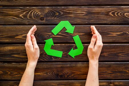 Recycling symbol in hands on wooden background top view