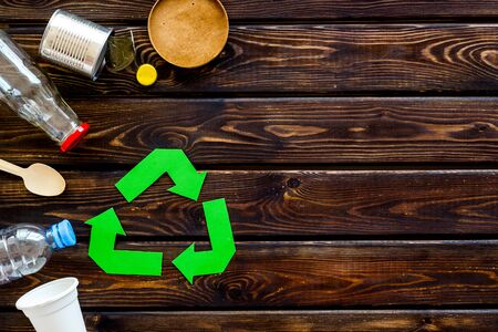 Recycling symbol and different garbage on wooden background top view copyspace