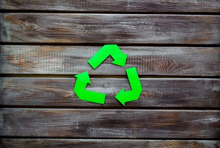 Recycling symbol for eco concept on wooden background top view