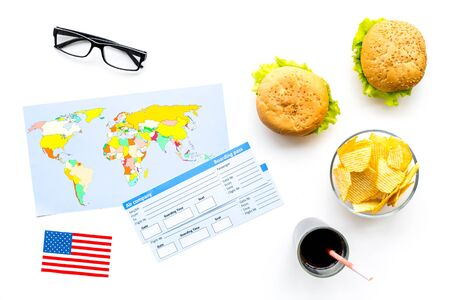 Gastronomical tourism with American flag, passport, tickets, map, burgers, chips on white background top view Banque d'images - 125127525