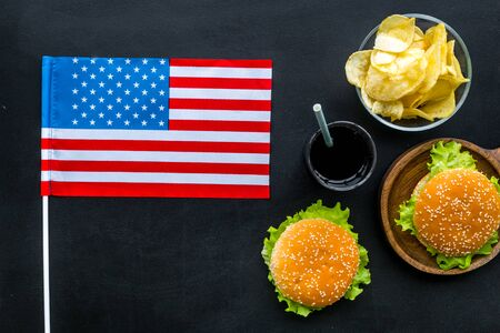 Independence Day of America concept with flag, burgers, chips and drink on black background top view
