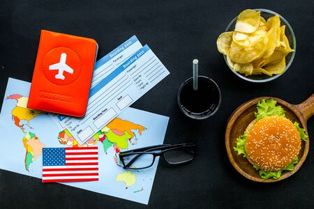 Travel for traditional USA cuisine with burgers, drink, chips, passport, tickets, flag and map black background top view Banque d'images - 125127531