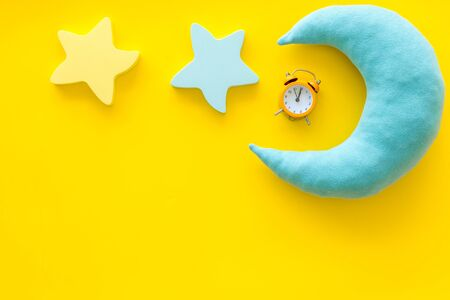 Sleep time concept with moon, stars, alarm clock on yellow background top view Foto de archivo