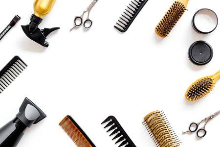 Peignes, ciseaux et outils de coiffeur dans le bureau de travail d'un salon de beauté sur fond blanc, espace de vue de dessus pour le texte Banque d'images