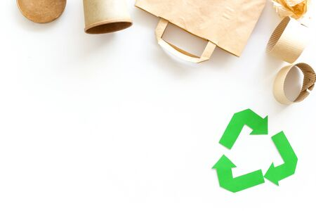 Ecology concept. Recycling symbol and paper garbage. Bag, cup on white background top view space for text