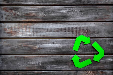 Recycling symbol for eco concept on wooden background top view copyspace