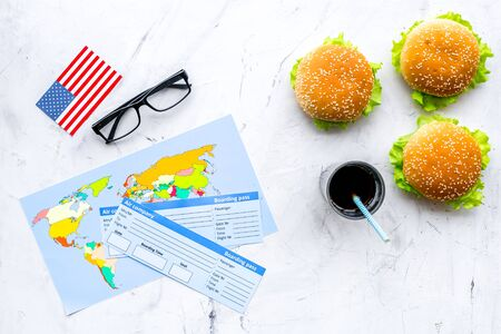 Gastronomical tourism with American flag, passport, tickets, map, burgers, chips, drink on marble background top view