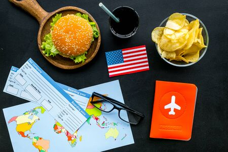 Gastronomical tourism with American flag, passport, tickets, map, burgers, chips, drink on black background top view