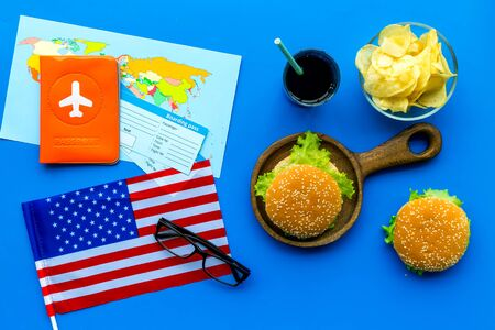 Gastronomical tourism with American flag, passport, tickets, map, burgers, chips, drink on blue background top view Stock Photo