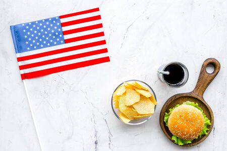 Flag USA and national food, burgers, chips and drink on marble background top view Stock Photo
