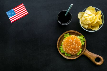 Independence Day of America concept with flag, burgers, chips and drink on black background top view copyspace Stock Photo