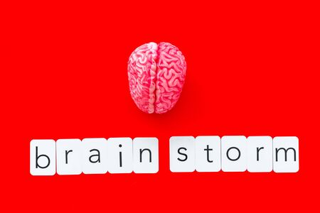 Brainstorm concept with brain on red background top view