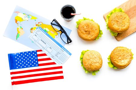 Travel for traditional USA cuisine with burgers, passport, tickets, flag and map white background top view Banque d'images - 125222163