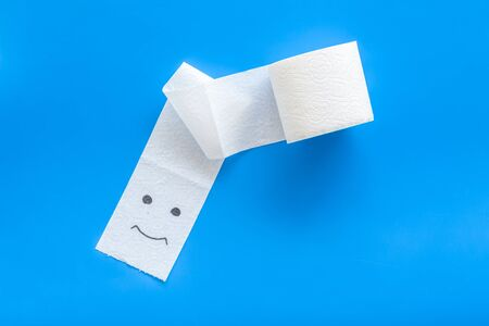 Toilet paper roll on blue background top view
