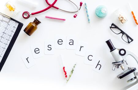 Do medical research with microscope, stethoscope, cardiogram, pills and test tube on white background top view Stock Photo