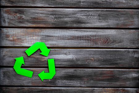 Recycling symbol for eco concept on wooden background top view copyspace.