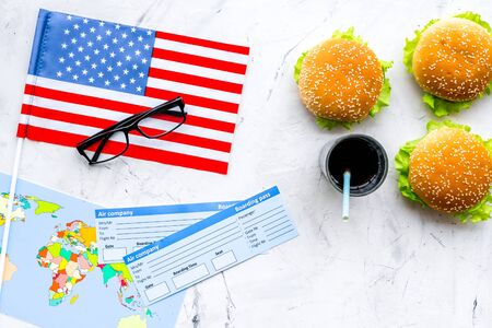 Traditional food. Burger, map, tickets and USA flag for gastronomical tourism to America on marble background top view Banque d'images - 125365398