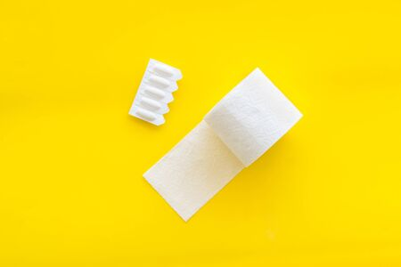 Disease of colon. Proctology concept with toilet paper roll and rectal suppository on yellow background top view