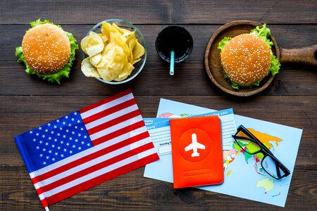 Traditional food. Burger, chips, map, tickets and USA flag for gastronomical tourism to America on wooden background top view