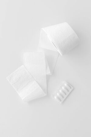 Disease of colon. Proctology concept with toilet paper roll and rectal suppository on white background top view