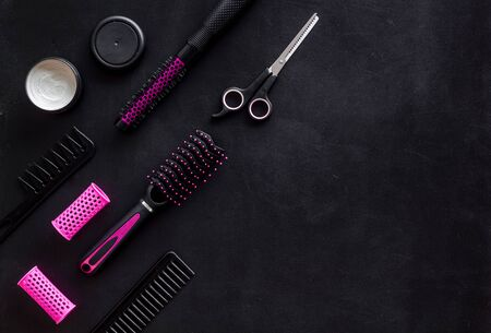 Hair styling concept. Combs, scissors and pink hairdresser tools on beauty salon work desk on black background top view mockup