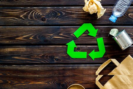 Green recycling symbol with paper bag, plastic bottle, can for ecology on wooden background top view copyspace
