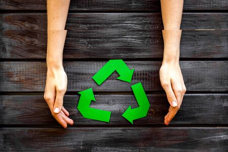Garbage disposal. Green recycling sign in hands for eco concept on wooden background top view