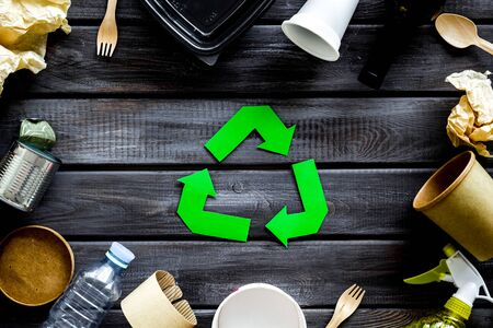 Ecology concept. Green recycling sign with waste materials, paper cup, plastic container, bottles, flatware on wooden background top view