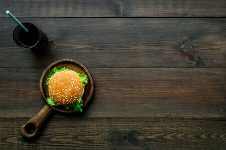 Traditional USA cuisine. National american food concept with burgers on pan and drink on wooden background top view copyspace