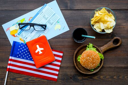 Traditional food. Burger, chips, map, tickets and USA flag for gastronomical tourism to America on wooden background top view Banque d'images - 125463864