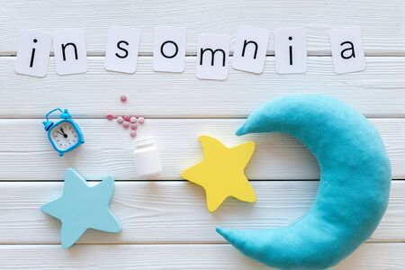 Try to sleep. Insomnia concept with moon, stars toy, alarm clock and pills on white wooden background top view