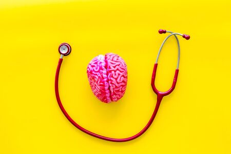 Mental diseases. Brain functions concept with brain and stethoscope on yellow background top view