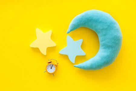 Aller au lit. Concept de temps de sommeil avec la lune, jouet d'étoiles, réveil sur la vue de dessus de fond jaune