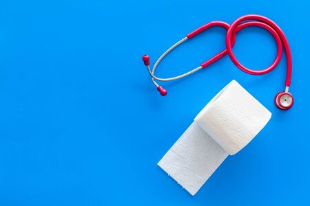 Disease of colon. Toilet paper roll and stethoscope for proctology diseases concept on blue background top view mock up Stock Photo