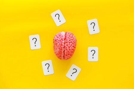 Discussion in office. Brain storm and business ideas concept with brain and question mark on yellow background top view Stock Photo