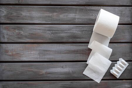 Disease of colon. Proctology concept with toilet paper roll and rectal suppository on wooden background top view mock-up