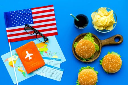 Gastronomical tourism concept with American flag, passport, tickets, map and food symbols, burgers, chips, drink on blue background top view Banque d'images - 125463947