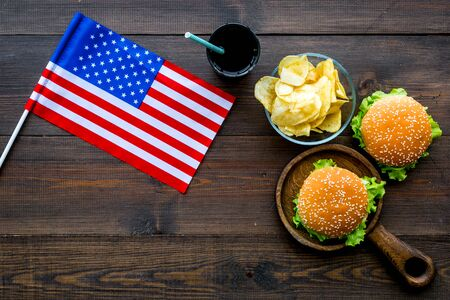 Independence Day of America celebration. Flag USA and national food, burgers, chips and drink on wooden background top view Reklamní fotografie
