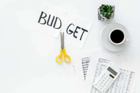 Business budget. Scissors and paper with word budget, coffee and plan for budget reducing on white background top view