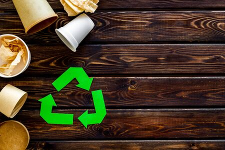 Green recycling symbol with paper and plastic cup for ecology on wooden background top view copyspace