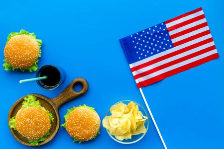 the 4th of July. Independence Day of America concept with flag, burgers, chips and drink on blue background top view