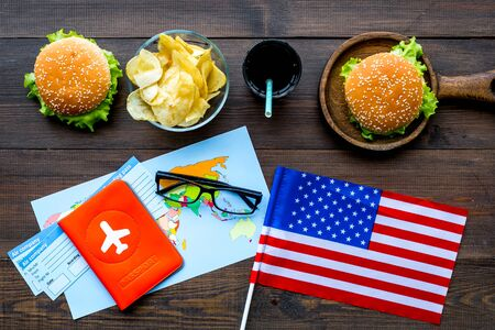 Gastronomical tourism concept with american flag, passport, tickets, map and food symbols, burgers, chips, drink on wooden background top view Banque d'images - 125564799