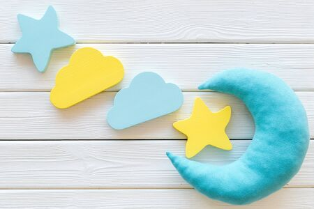 Go to bed. Sleep time concept with moon, stars, clouds toy on white wooden background top view