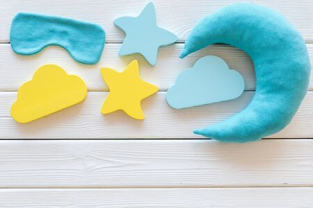 Go to bed. Sleep time concept with moon, stars, clouds toy, blind folder on white wooden background top view 版權商用圖片