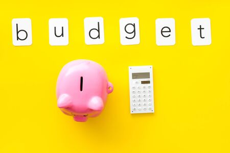 Piggy bank. Moneybox in shape of pig and calculator for business budget on yellow background top view