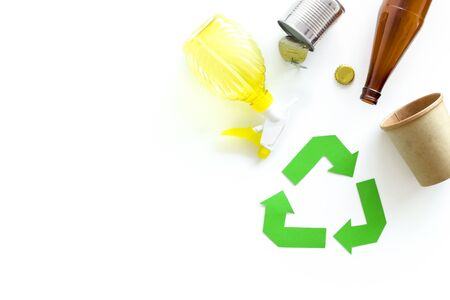 Eco friendly. Green recycling sign with waste materials, bottle, cups, can for ecology save concept on white background top view copyspace